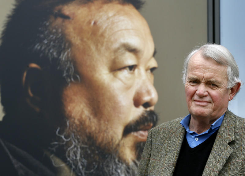 "In this photo taken Thursday, April 11, 2013, playwright Howard Brenton, author of a play about Chinese contemporary artist Ai Weiwei  called '#aiww: The Arrest of Ai Weiwei' stands by a poster for his play at Hampstead Theatre in London. Brenton, 70, is one of Britain's best-known playwrights, whose work has ranged from provocative history play ""The Romans in Britain"" - the focus of a famous, failed prosecution for obscenity in 1982 - to journalism satire ""Pravda,"" co-written with David Hare. (AP Photo/Kirsty Wigglesworth)"