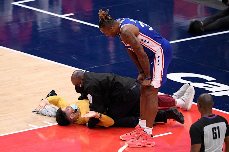 Philadelphia 76ers center Dwight Howard watches as a fan who ran onto the court is restrained by security personnel during the second half of Monday's game.