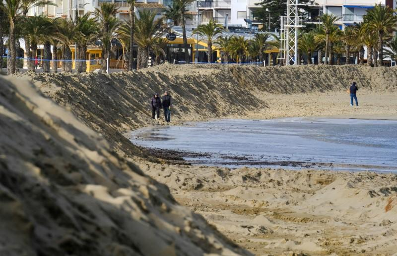 """People walk past a huge sand shaft built to to protect the Arenal Beach ahead of the upcoming storm """"Gloria"""", in Javea near Alicante"""