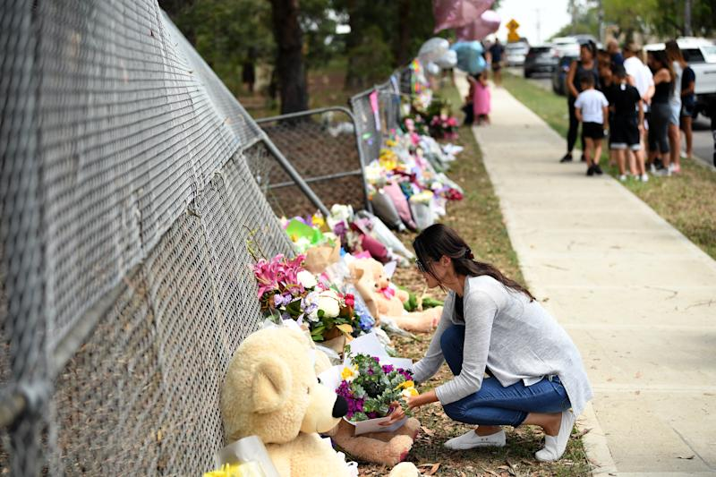 A woman places flowers at the scene of the accident in Sydney's western suburb of Oatlands.