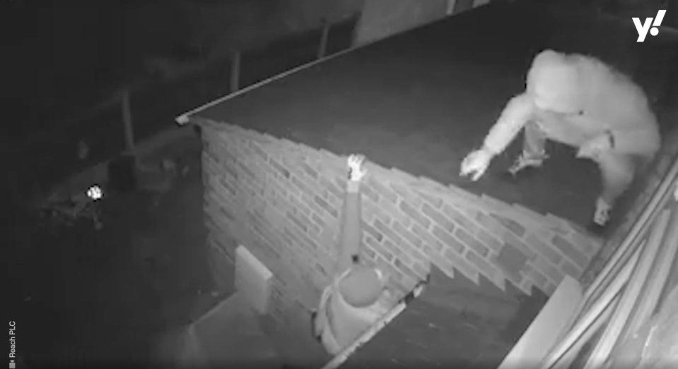 One of the burglars falls as he tries to climb onto the roof. (Reach)