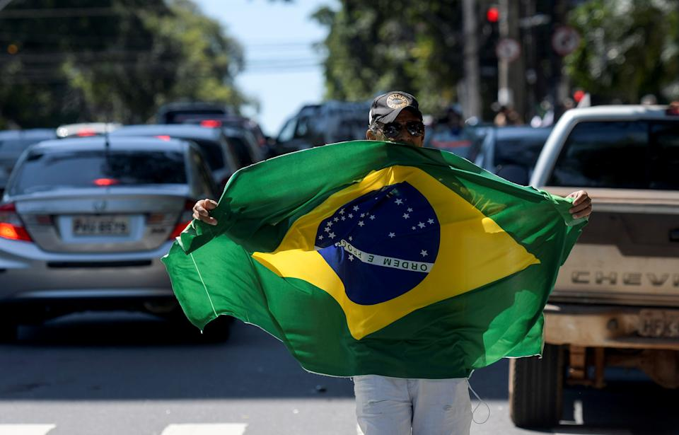 A demonstrator holds a Brazilian flag during protest against authorities' measures on the new coronavirus disease (COVID-19) outbreak and in support of Brazil's President Jair Bolsonaro in Belo Horizonte, Brazil April 21, 2020. REUTERS/Washington Alves
