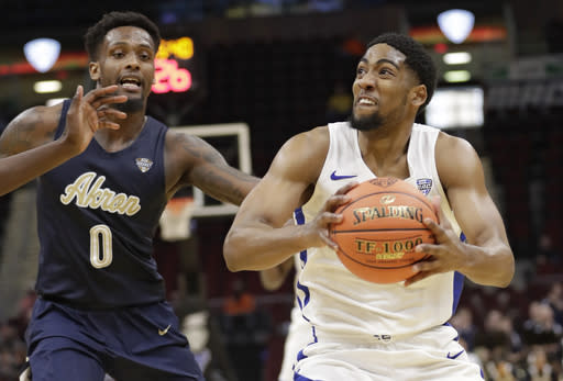 Buffalo's CJ Massinburg (5) drives to the basket against Akron's Jimond Ivey (0) during the second half of an NCAA college basketball game at the Mid-American Conference tournament, Thursday, March 14, 2019, in Cleveland. (AP Photo/Tony Dejak)