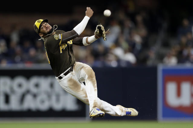 San Diego Padres shortstop Fernando Tatis Jr. overthrows first as Cincinnati Reds' Jose Iglesias arrives safely on the throwing error during the 11th inning of a baseball game Friday, April 19, 2019, in San Diego. (AP Photo/Gregory Bull)
