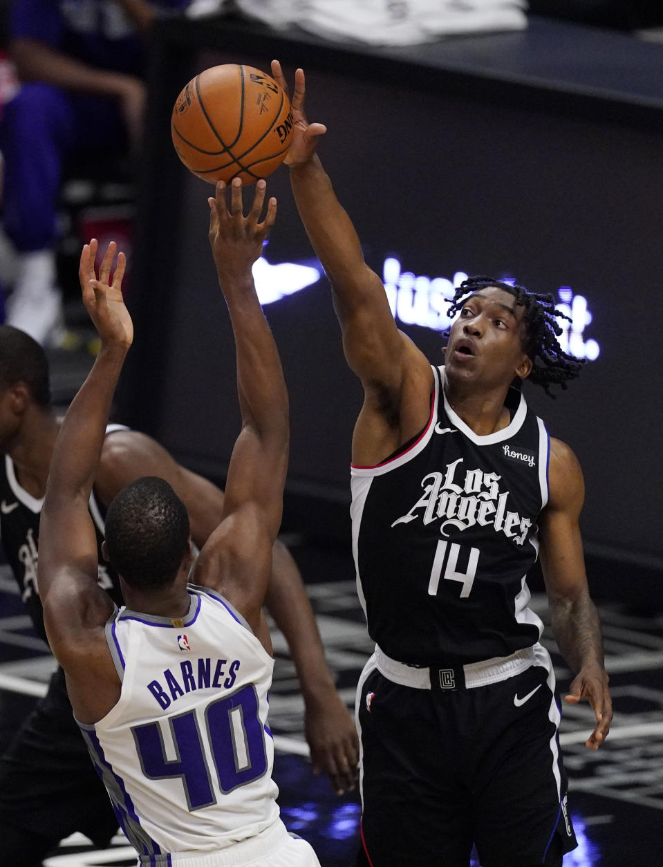 Sacramento Kings forward Harrison Barnes, left, shoots as Los Angeles Clippers guard Terance Mann defends during the first half of an NBA basketball game Sunday, Feb. 7, 2021, in Los Angeles. (AP Photo/Mark J. Terrill)