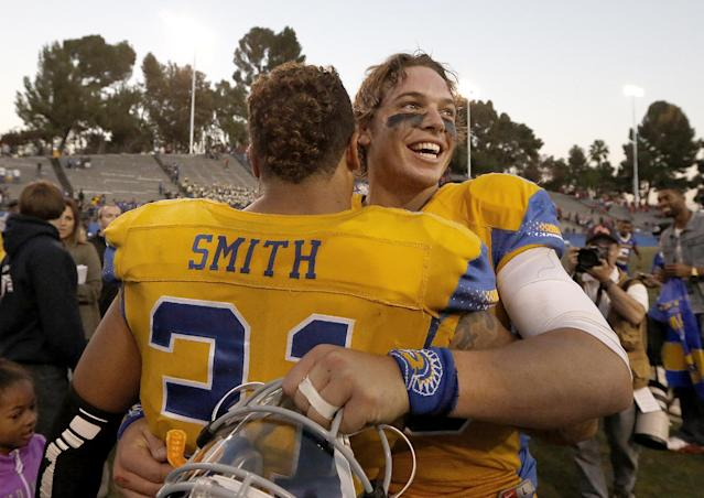 San Jose State quarterback David Fales, right, celebrates with teammate Keith Smith (31) after a 62-52 victory against Fresno State in an NCAA college football game on Friday, Nov. 29, 2013, in San Jose, Calif. (AP Photo/Tony Avelar)