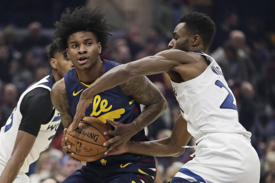 Cleveland Cavaliers' Kevin Porter Jr., left, drives past Minnesota Timberwolves' Andrew Wiggins in the first half of an NBA basketball game, Sunday, Jan. 5, 2020, in Cleveland. (AP Photo/Tony Dejak)