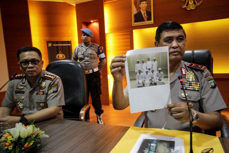Riau Island Police chief Sam Budigusdian holding up a picture of eight suspects who were deported from Malaysia, during a press conference in Batam on Wednesday (11 January). (PHOTO: Reuters)