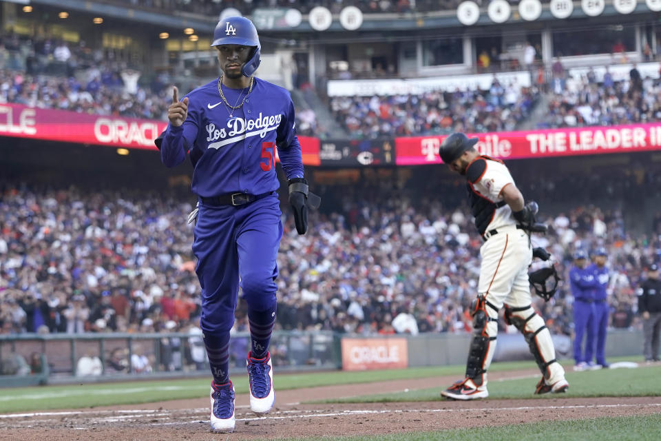 Los Angeles Dodgers' Mookie Betts, left, scores in front of San Francisco Giants catcher Curt Casali after pitcher Camilo Doval walked Will Smith with the bases during the fifth inning of a baseball game in San Francisco, Sunday, Sept. 5, 2021. (AP Photo/Jeff Chiu)