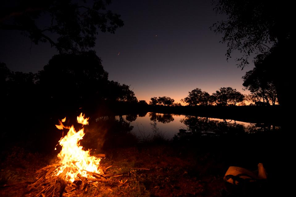 A campfire at the Darling River at sunset in the NSW outback town of Bourke