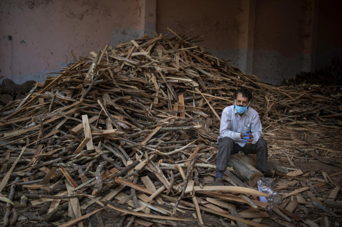 A man sits on a log while waiting for the funeral of his relative who died of COVID-19, at a ground that has been converted into a crematorium for mass cremation of COVID-19 victims in New Delhi, India, Saturday, April 24, 2021. Delhi has been cremating so many bodies of coronavirus victims that authorities are getting requests to start cutting down trees in city parks, as a second record surge has brought India's tattered healthcare system to its knees. (AP Photo/Altaf Qadri)