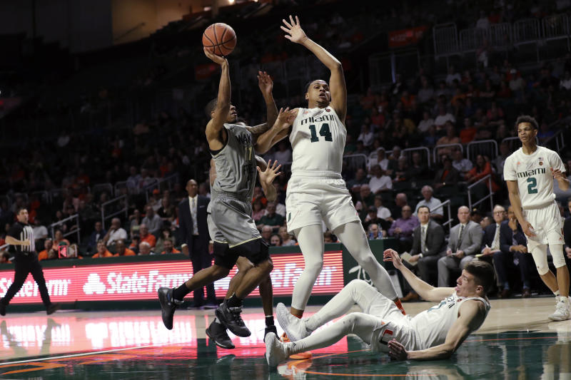 Wake Forest guard Torry Johnson (11) goes up for a shot against Miami center Rodney Miller Jr. (14) and guard Dejan Vasiljevic (1) during the second half of an NCAA college basketball game, Saturday, Feb. 15, 2020, in Coral Gables, Fla. Miami defeated Wake Forest 71-54. (AP Photo/Wilfredo Lee)