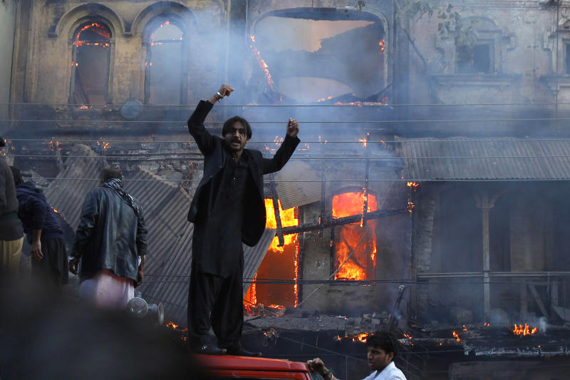 A Shiite Muslim shouts slogans in front of a burning market outside an Islamic seminary set on fire by angry Shiite mob during clashes with Sunni Muslims in Rawalpindi, Pakistan. Friday, Nov. 15, 2013. Police in Pakistan say Shiite Muslims staging a religious procession beat three Sunnis to death after the two sides clashed. (AP Photo/Anjum Naveed)