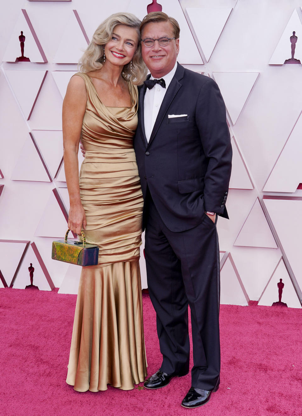 Paulina Porizkova wearing a gold dress on the red carpet with partner Aaron Sorkin at the 93rd Annual Academy Awards at Union Station on April 25, 2021 in Los Angeles, California