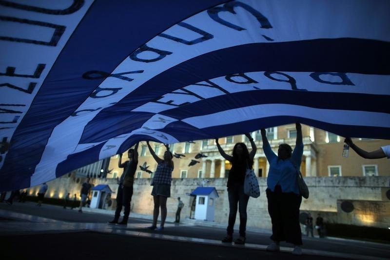 Anti-austerity demonstrators hold up a giant Greek flag front of parliament in Athens