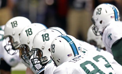 Tulane football players wear the number 18 on their helmets honoring Tulane safety Devon Walker, who fractured his spine against Tulsa on Sept. 8, before the start of their NCAA college football game against Mississippi in New Orleans, Saturday, Sept. 22, 2012. (AP Photo/Bill Haber)