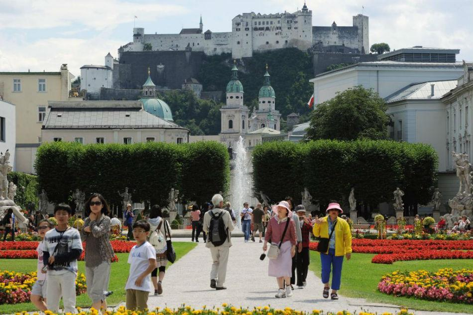 Tourists visit Mirabell Gardens with Fortress Hohensalzburg in the background.