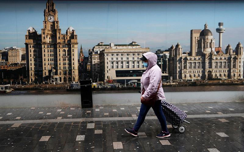 A woman wearing a face mask walks on the street in Liverpool - REUTERS/Phil Noble