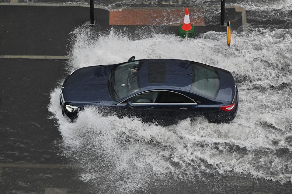 A car drives through deep water on a flooded road in The Nine Elms district of London on July 25, 2021 during heavy rain. - Buses and cars were left stranded when roads across London flooded on Sunday, as repeated thunderstorms battered the British capital. (Photo by JUSTIN TALLIS / AFP) (Photo by JUSTIN TALLIS/AFP via Getty Images)