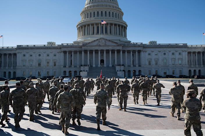 <p>Members of the National Guard are seen on the East Front of the US Capitol Building on Capitol Hill 2 March 2021, in Washington, DC</p> ((AFP via Getty Images))