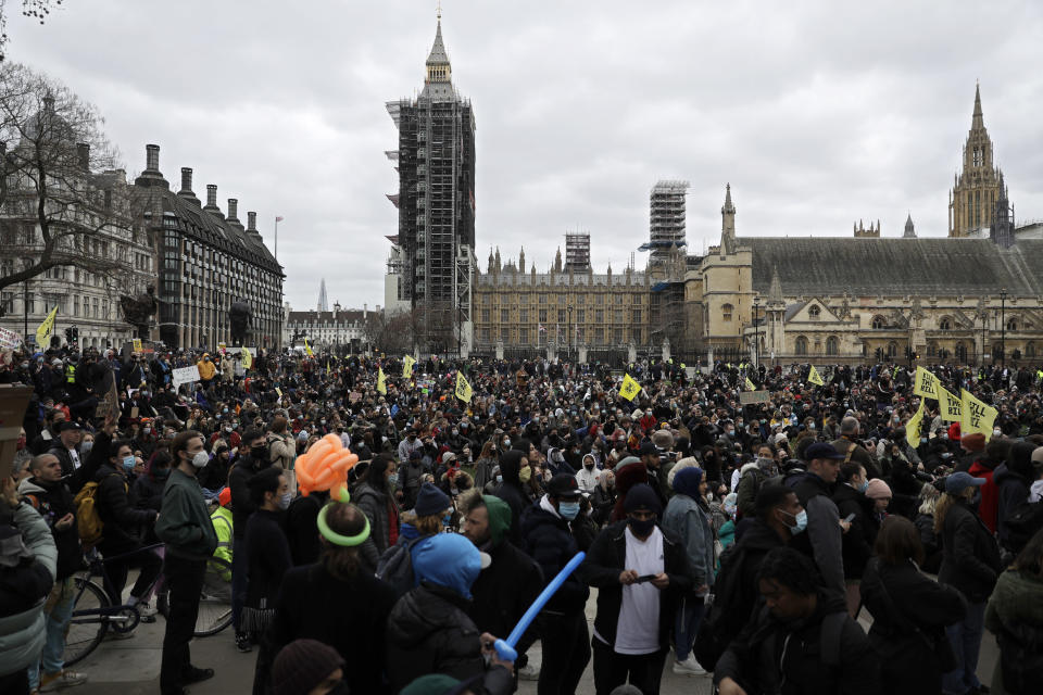 Demonstrators holding posters and flags gather at Parliament Square during a 'Kill the Bill' protest in London, Saturday, April 3, 2021. The demonstration is against the contentious Police, Crime, Sentencing and Courts Bill, which is currently going through Parliament and would give police stronger powers to restrict protests. (AP Photo/Matt Dunham)