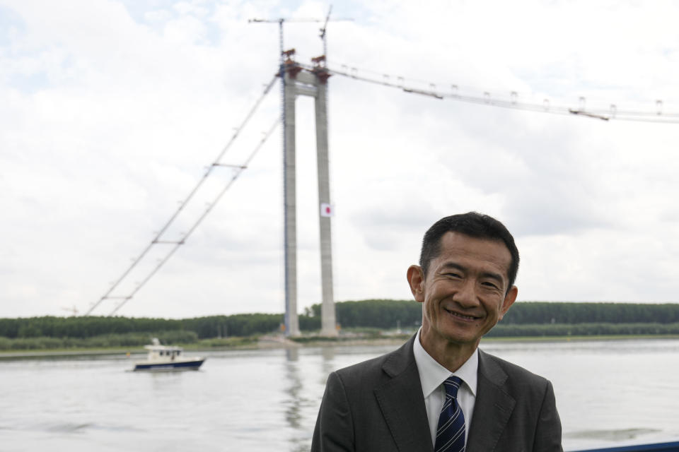 Japanese ambassador to RomaniaHiroshi Ueda poses during a ceremony marking 100 years of diplomatic relations between Japan and Romania, at the construction site of a suspension bridge over the Dnube river in Braila, Romania, Thursday, Aug. 26, 2021. The bridge, built by Japanese and Italian companies, with a span of 1,974.3 meters, will be the largest of its kind in Romania and the third in the European union.(AP Photo/Vadim Ghirda)