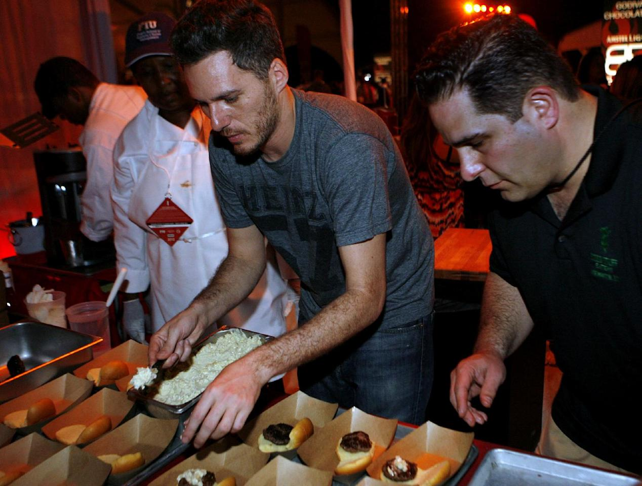Spike Mendelsohn of Good Stuff Eatery, center, works on his creation while competing in the Burger Bash at the Food Network South Beach Wine & Food Festival in Miami Beach, Fla., Friday, Feb. 24, 2012. (AP photo/Jeffrey M. Boan)