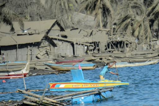 A fisherman paddles his wooden boat next to houses and coconut tress covered in mud and ash due to the eruption of the nearby Taal volcano