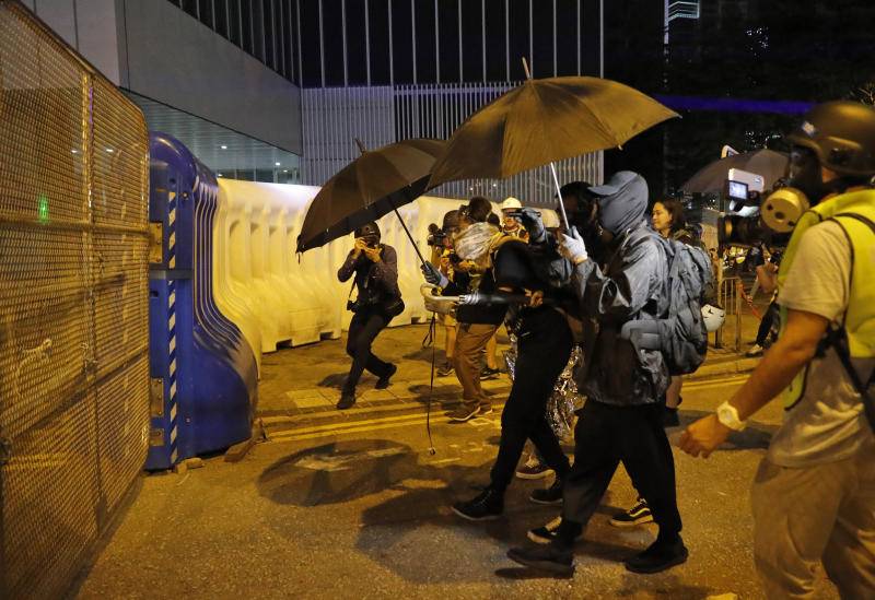 Black-clad protesters wearing goggles and masks approach barricades outside government offices in Hong Kong, Saturday, Sept. 28, 2019. Thousands of people gathered Saturday for a rally in downtown Hong Kong, belting out songs, speeches and slogans to mark the fifth anniversary of the start of the 2014 Umbrella protest movement that called for democratic reforms in the semiautonomous Chinese territory. (AP Photo/Vincent Thian)
