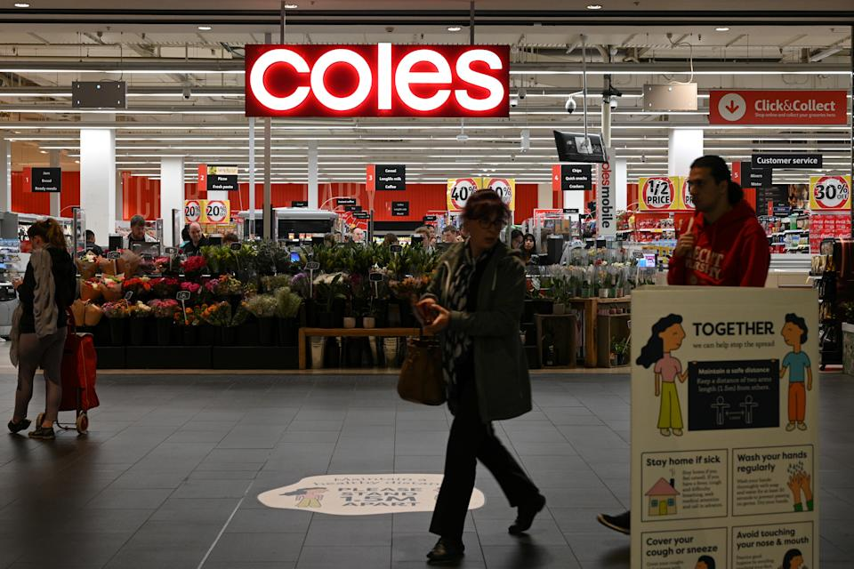 A person walks outside a Coles store.