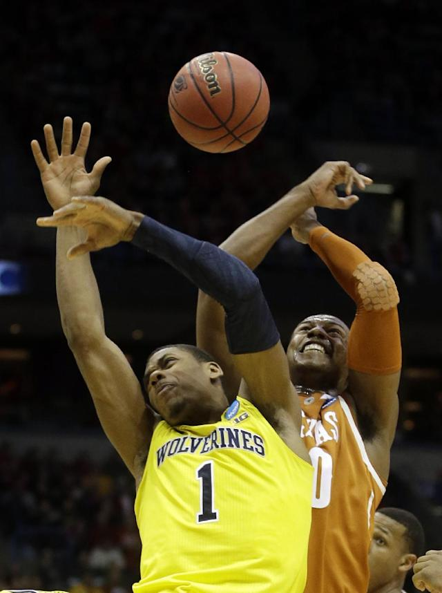 Michigan forward Glenn Robinson III (1) and Texas forward Jonathan Holmes (10) battle for a rebound during the second half of a third-round game of the NCAA college basketball tournament Saturday, March 22, 2014, in Milwaukee. (AP Photo/Morry Gash)
