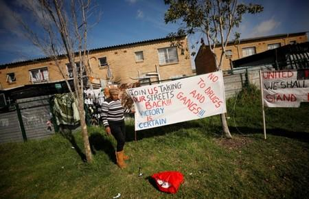 A resident puts up a banner as community members gather in a park to discuss gang violence in Manenberg township, Cape Town
