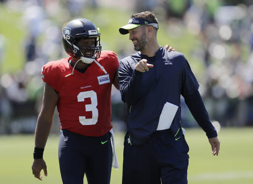 Seattle Seahawks quarterback Russell Wilson (3) talks with offensive coordinator Brian Schottenheimer, right, Monday, July 29, 2019, following NFL football training camp in Renton, Wash. (AP Photo/Ted S. Warren)