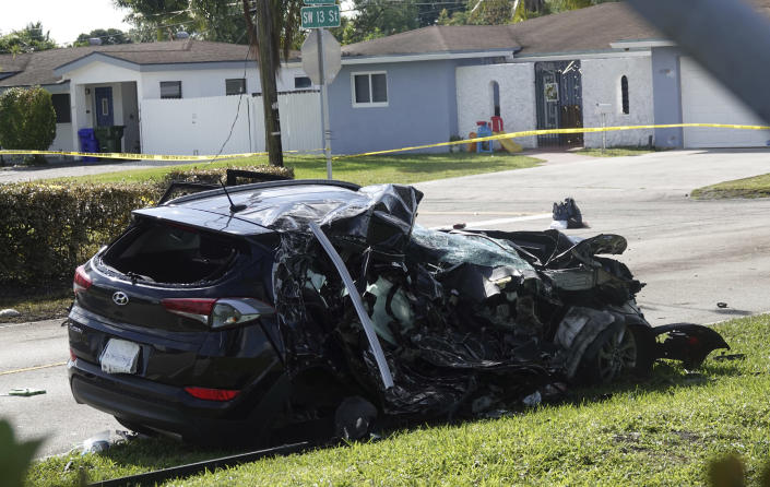 The SUV which was struck by an airplane Monday is seen behind police lines on a residential street near North Perry Airport in Pembroke Pines, Tuesday, March 16, 2021. A four-year-old child riding in the vehicle and the pilot and passenger in the plane were killed. (Joe Cavaretta/South Florida Sun-Sentinel via AP)