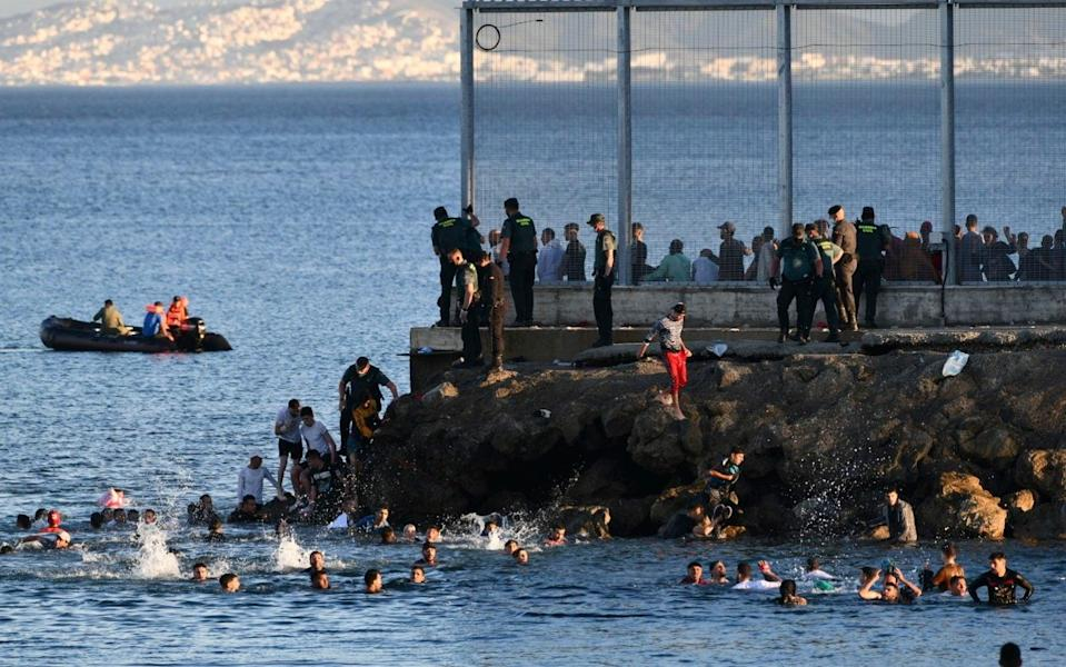 Migrants swim around the border between Morocco and the Spanish enclave of Ceuta