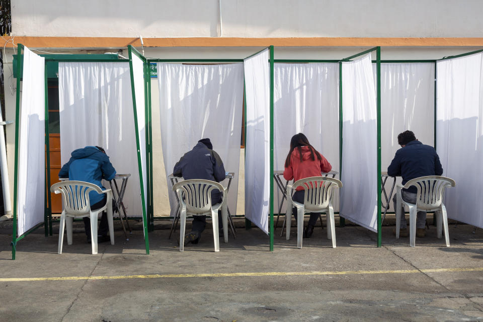Exile Tibetans sit inside booths to mark their choices on election papers in Dharmsala, India, Sunday, Jan. 3, 2021. Exile Tibetans Sunday voted in the first round to elect a new political leader and members of the Tibetan parliament in exile. (AP Photo/Ashwini Bhatia)
