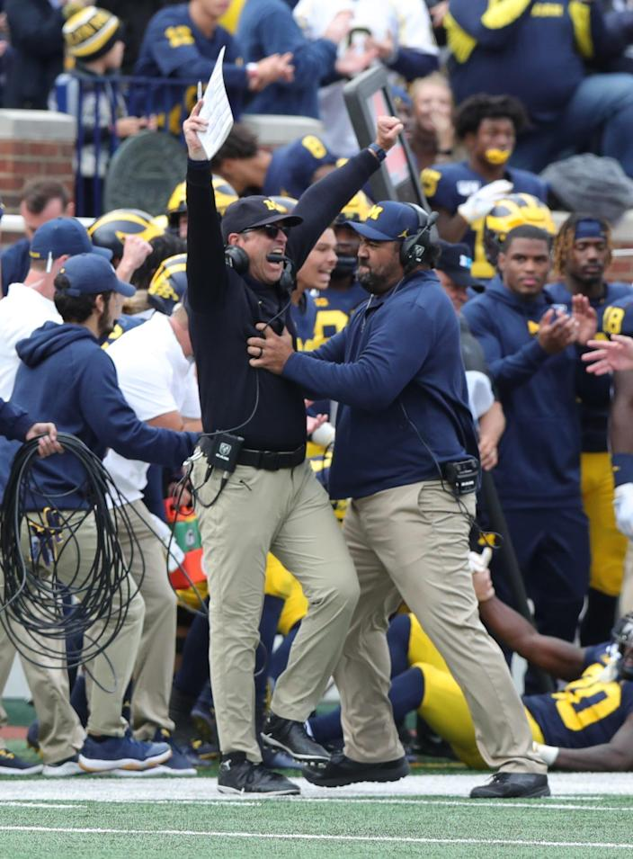 Michigan coach Jim Harbaugh and defensive line coach Shaun Nua celebrate after the defense holds off Iowa on fourth down in the final seconds of U-M's 10-3 win on Saturday, Oct. 5, 2019, at Michigan Stadium.