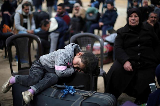 <p>A girl sleeps on a suitcase as she waits with her family for a travel permit to cross into Egypt through the Rafah border crossing after it was opened by Egyptian authorities for humanitarian cases, in the southern Gaza Strip, Feb. 8, 2018. (Photo: Ibraheem Abu Mustafa/Reuters) </p>