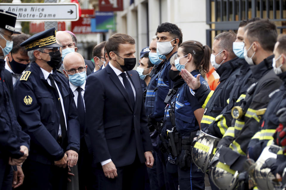 French President Emmanuel Macron (centre) with police officers and rescue workers after a knife attack at Notre Dame church in Nice.