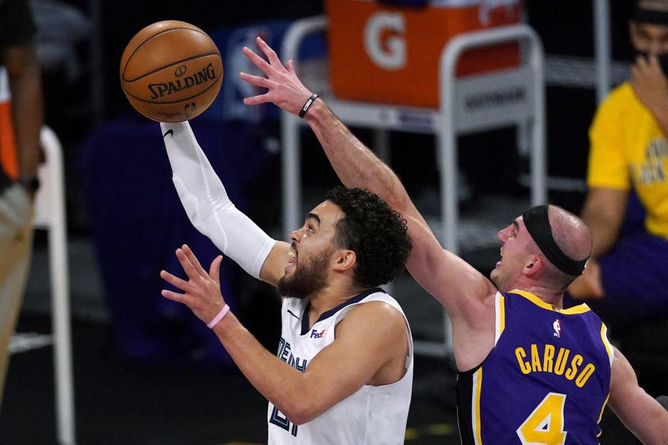 Memphis Grizzlies guard Tyus Jones, left, shoots as Los Angeles Lakers guard Alex Caruso defends during the first half of an NBA basketball game Friday, Feb. 12, 2021, in Los Angeles. (AP Photo/Mark J. Terrill)