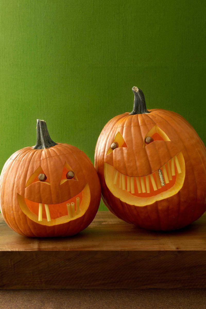 <p>Carve an opening out of the top or bottom of the pumpkin and scoop out the seeds. Replace the cutout. Draw eyes and mouth on the pumpkin with the marker and carve out. Wipe off any remaining marker with a damp cloth.</p><p>Place a dab of hot glue inside a dry ziti piece and press the cut end of half of a toothpick into the glue. Let dry. Repeat on 5 to 15 ziti pieces; set one aside. Insert remaining ziti teeth into the pumpkin's mouth with the exposed end of the picks, leaving space for the last tooth. To create the gold tooth, coat the ziti piece you've set aside in white glue and roll in glitter. Let dry. Shake off excess. Insert into the open space in the pumpkin's mouth. Wedge nuts into openings for eyes.</p>