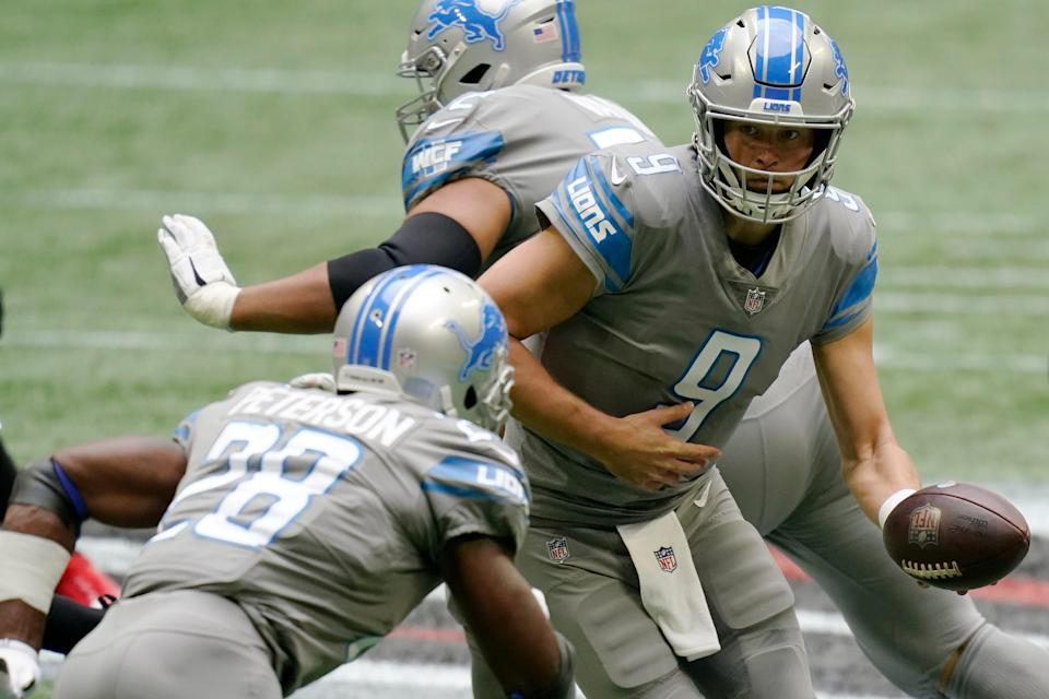 Lions quarterback Matthew Stafford hands the ball off to Lions running back Adrian Peterson against the Falcons during the first half on Sunday, Oct. 25, 2020, in Atlanta.