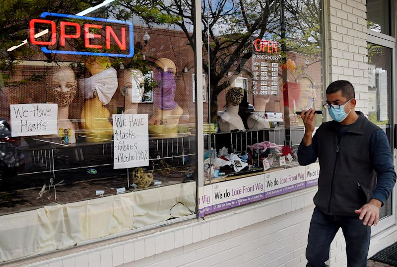 A man walks past mannequin heads wearing masks in the window of a small boutique advertising availability of masks, gloves, and other pandemic necessities amid the Coronavirus outbreak in Arlington, Virginia, on April 27, 2020. - Several states have seen protests against stay-at-home orders and Georgia has allowed thousands of businesses to resume operations, against the advice of health experts. (Photo by Olivier DOULIERY / AFP) (Photo by OLIVIER DOULIERY/AFP via Getty Images)