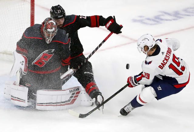 Carolina Hurricanes' Justin Faulk (27) assists goaltender Petr Mrazek (34) of the Czech Republic, in blocking the shot of Washington Capitals' Nicklas Backstrom (19) of Sweden, during the third period of Game 4 of an NHL hockey first-round playoff series in Raleigh, N.C, Thursday, April 18, 2019, (AP Photo/Karl B DeBlaker)
