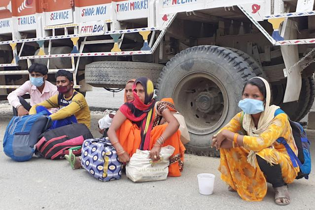 In this photo taken on May 13, 2020, migrant labourer Manish Verma (2nd L) sits along with his family and neighbours on the national highway during a government-imposed nationwide lockdown as a preventive measure against the COVID-19 coronavirus, in Ghaziabad. - Indian Prime Minister Narendra Modi's grand announcement of a $265-billion rescue package for the Indian economy is little comfort to Manish Verma, one of millions left destitute and desperate 50 days into a crippling coronavirus lockdown. (Photo by Abhaya SRIVASTAVA / AFP) (Photo by ABHAYA SRIVASTAVA/AFP via Getty Images)