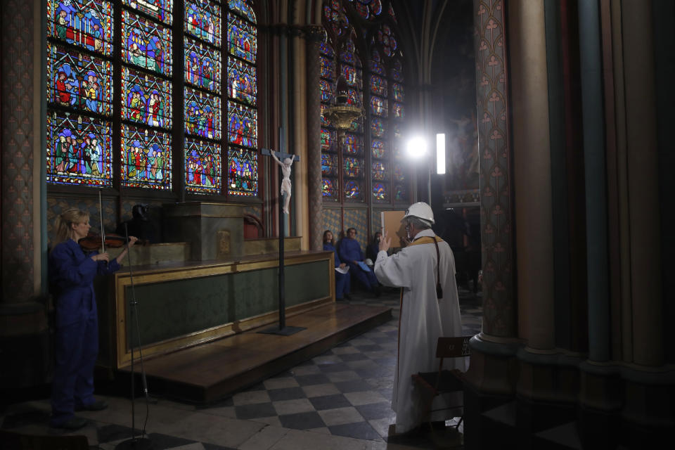 Notre Dame rector Patrick Chauvet hold a Bible as part of the Maundy Thursday ceremony while while French cellist Marina Chiche performs in Notre Dame Cathedral, Thursday, April 1, 2021, almost two years after a massive fire ravaged the Gothic cathedral. (AP Photo/Christophe Ena, Pool)