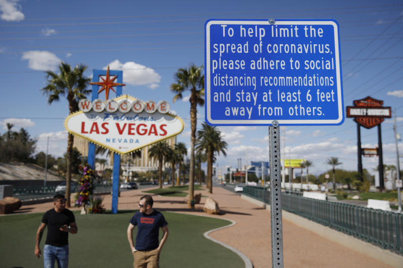 """FILE - In this March 21, 2020 file photo, a sign advises people to practice social distancing to slow the spread of the coronavirus at the """"Welcome to Fabulous Las Vegas Nevada"""" sign amid a shutdown of casinos along the Las Vegas Strip in Las Vegas. Nervous travelers, spotty air service, health risks _  the battered global tourism industry is facing unprecedented uncertainty in the wake of the new coronavirus. Millions of workers are laid off or furloughed, and it will likely take years for the industry to get back to the strong demand it was seeing just six months ago. (AP Photo/John Locher, File)"""