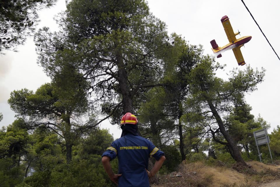 An aircraft operates as a firefighter looks on during a wildfire in Ippokratios Politia village, about 35 kilometres (21 miles) north of Athens, Greece, Friday, Aug. 6, 2021. Thousands of people fled wildfires burning out of control in Greece and Turkey on Friday, as a protracted heat wave turned forests into tinderboxes and flames threatened populated areas, electricity installations and historic sites. (AP Photo/Thanassis Stavrakis)