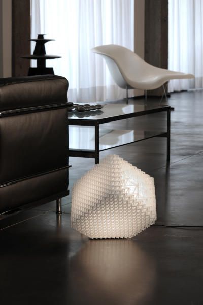In this photo provided by .MGX by Materialise, the Volume.MGX lamp by Dror, from the design division of Belgium-based 3-D printing company, Materialise, expands from a flattened position to create a shape which, when lit, provides both a bright, warm glow in its center and a cooler, darker feeling around its edges. A novelty once reserved for science-fiction, 3-D printing has gone mainstream in home decor thanks to cheaper, more accessible technology. (AP Photo/MGX by Materialise)