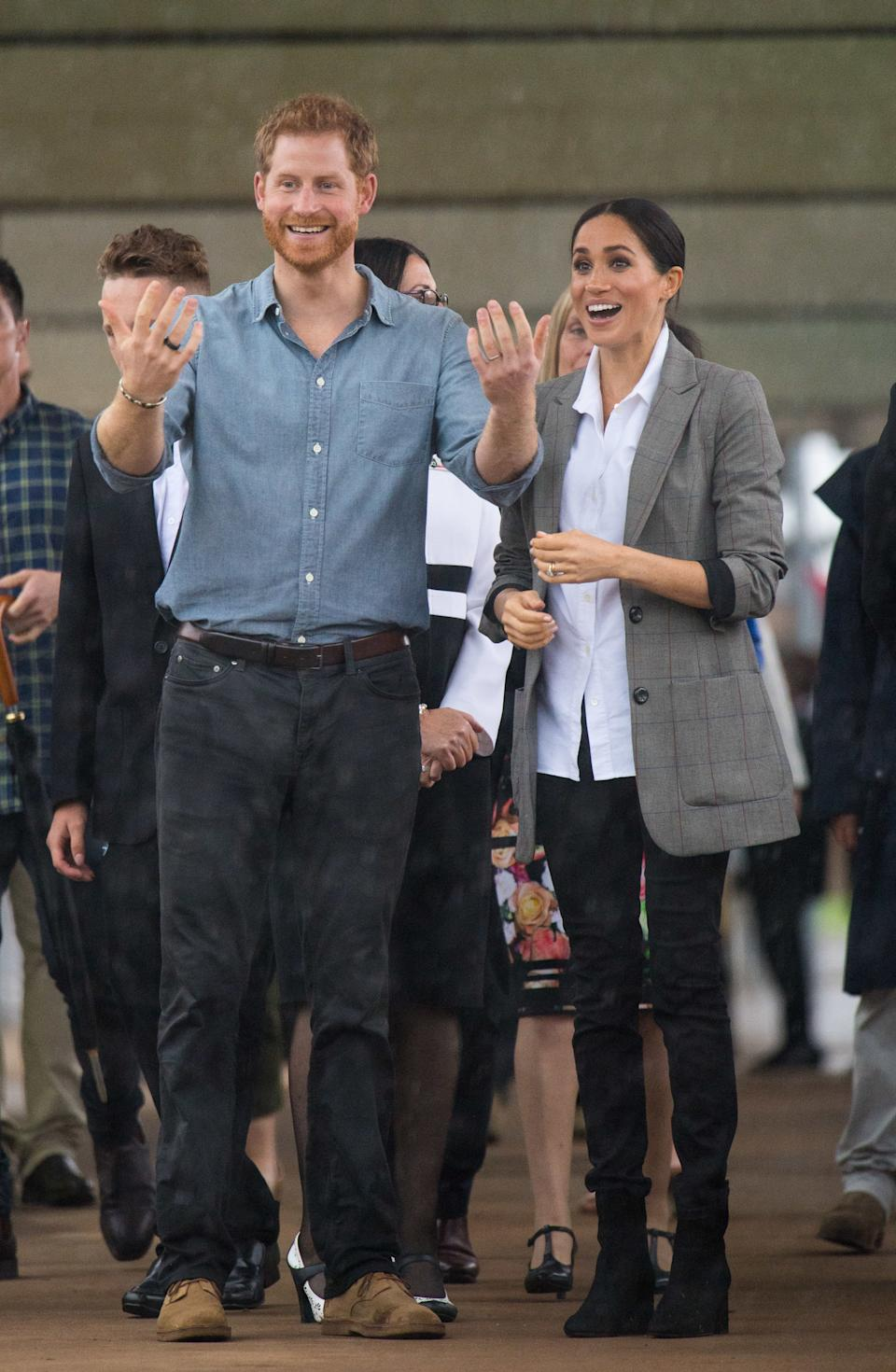The Duke and Duchess of Sussex look out at a heavy downpour of rain during a visit to Clontarf Foundation and Girls Academy in Dubbo, New South Wales, on the second day of the royal couple's visit to Australia. (Photo by Dominic Lipinski/PA Images via Getty Images)